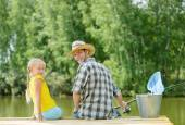 Father and daughter sitting at bridge — Stock Photo
