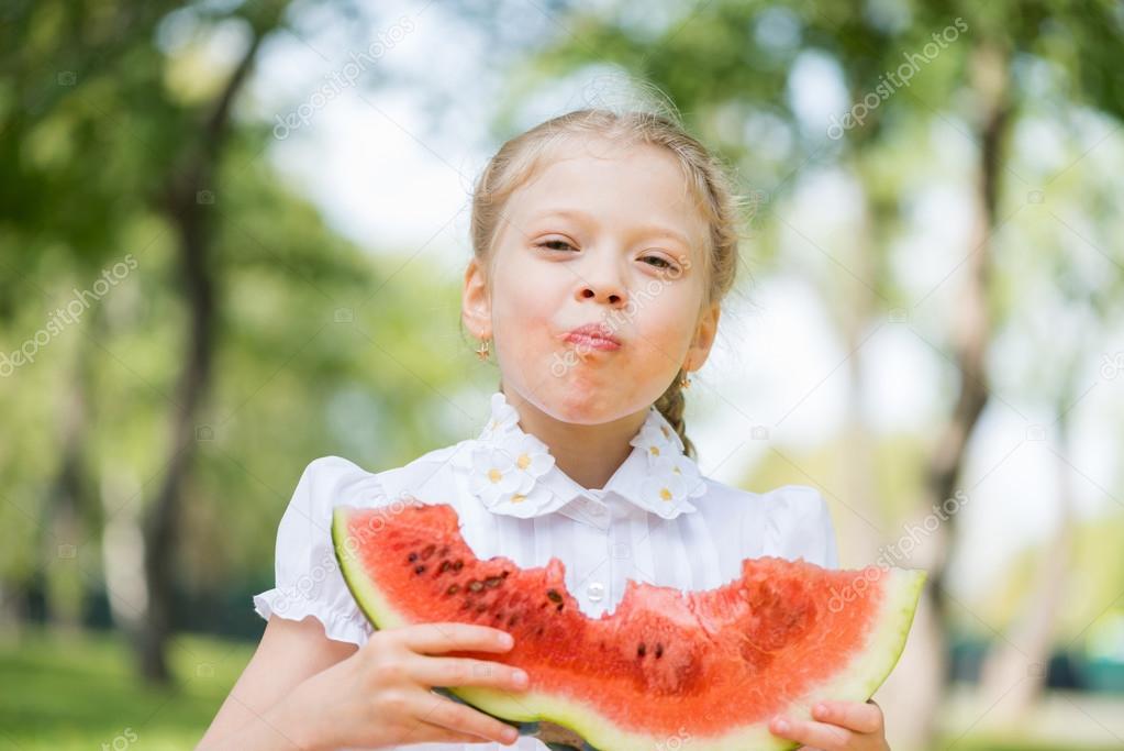 可爱的小女孩坐在公园里,吃西瓜.