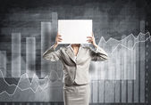 Businesswoman hiding her face behind paper — Stock Photo
