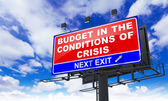 Budget in the Conditions of Crisis on Red Billboard. — Stock Photo