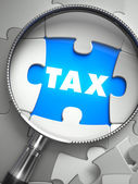 Tax - Missing Puzzle Piece through Magnifier. — Stock Photo