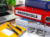 Red Ring Binder with Inscription Protocols. — Stock Photo
