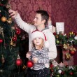 Father and daughter illuminate a Christmas tree by big bright red and golden balls. A girl with Santa Claus red hat on her head keeps a red ball. There are a fireplace behind them. — Stock Photo #60544661