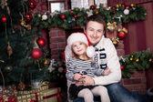 Vater umarmt Tochter in der Nähe der Weihnachtsbaum. Die Mädchen hält eine kleine Kugel und gibt es ein Weihnachtsmann-Hut auf dem Kopf. Ein Kamin hinter Ihnen. — Stockfoto