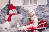 A little girl on the sleigh with red fir-tree ball in her hands. Backside decorated by  imitation of snow and snowman near the brick wall — Stock Photo
