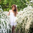 Charming young lady stands full-length in spring garden full of white flowers — Stock Photo #63109259
