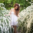Charming young lady stands full-length in spring garden full of white flowers — Stock Photo #63109269