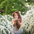 Beautiful young lady in spring garden full of white flowers. She inflates flower petals from her hands — Stock Photo #63109275