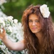 Portrait of charming young woman with beautiful smile in spring garden full of white flowers — Stock Photo #63109289
