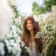 Portrait of charming young woman with beautiful smile in spring garden full of white flowers — Stock Photo #63109303