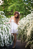 Charming young lady stands full-length in spring garden full of white flowers — Stock Photo