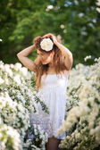 Charming young lady lifts up hel long curly dark hair in spring garden full of white flowers — Foto Stock