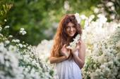 Charming young lady with beautiful smile keeps flowering branch in spring garden full of white flowers — Stock Photo