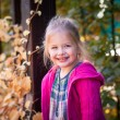 Smiling funny little girl in bright clothes — Stock Photo #63164381