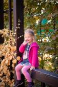 Smiling funny little girl in bright clothes picking her nose — Stock Photo