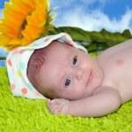 Portrait of cute happy baby, lying on green carpet — Stock Photo #53399111