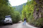 Young woman posing near the car in forest — Stock Photo