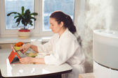 Woman sitting with tablet PC on the background of humidifier — Stock Photo
