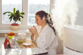 Woman drinking tea reading tablet at humidifier — Stock Photo