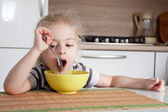 Littke girl is thinking while eating and doesn't want to eat — Stock Photo