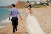 Wedding couple, bride and groom, walking on a beautiful beach — Стоковое фото