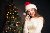 Woman calling mobile in front of Christmas tree — Stock Photo