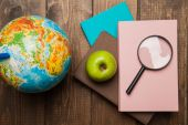 Globe, stack of books and magnifier on wood — Stock Photo