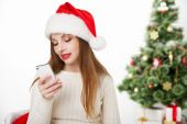 Girl in santa hat call phone by christmas tree — Foto Stock