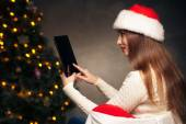 Woman sitting with tablet PC over Christmas tree — Stock Photo