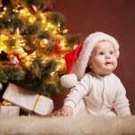 Happy baby wearing Santa hat over christmas tree — Stock Photo #58819131