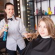 Hairstylist with hairspray and female client — Stock Photo #79817424
