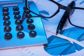 Pen, calculator and glasses in the blue light of the monitor — Stock Photo