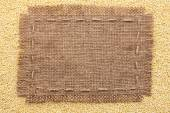 Frame of burlap  lying on a millet  background — Stock Photo