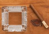 Glass ashtray with cigar  on a wooden surface — Stok fotoğraf