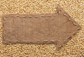 Pointer of burlap with place for your text, lying on a barley  — Stock Photo