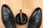 Classic men's shoes, ashtray and  fuming cigar on the wooden floor — Stock Photo