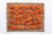 Frame made of burlap with dried apricots — Stock Photo