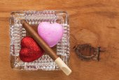 Love and harmful habit in a glass ashtray — Stock Photo