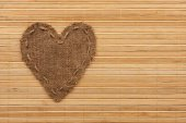 The symbolic heart of burlap lies on a bamboo mat — Stock Photo