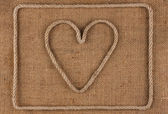 Heart made of rope on burlap — Stock Photo