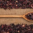 Wooden spoon with  dried hibiscus lies on  sackcloth — Stock Photo #66735857