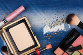 Still life from cosmetics on ragged jeans with rhinestones — Stock Photo