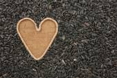 Symbolic heart made of rope lies on sackcloth and sunflower seed — Stock Photo