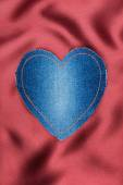 Heart of denim fabric with yellow stitching on red silk — Stock Photo