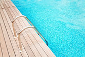 Blue swimming pool with metal hand-rails  and wooden decking  — Stock Photo