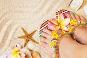 Female feet with pretty multicolor pedicure on sand, with frangi — Stockfoto