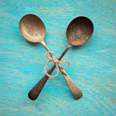 Two Old crossed vintage spoons on blue wooden background, top vi — Stock Photo