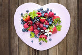 Mix of fresh berries in three  glass ramekins in shape of heart, — Stock Photo