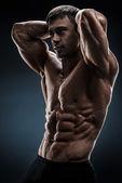 Gut aussehend Muskel Bodybuilder posing auf schwarzem Hintergrund — Stockfoto
