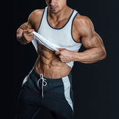 Athletic male model posing, pulling up tank top — Stock Photo